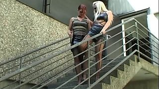 Claudia and Katerina wear black for an outdoor lesbian game