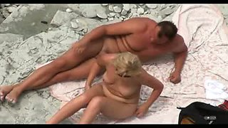 Mature couple has fun on the beach. Voyeur