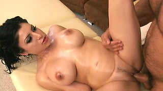 Oiled up brunette bitch with big balloons rides a terrific cock