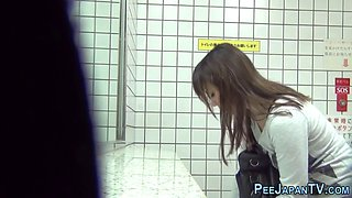 Adorable kinky Asian teens are being spied on while pissing in a public toilet