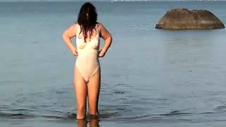 Attractive brunette milf flaunts her curves on the beach