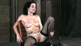 Slender pale and tattooed brunette rides sex machine while being tied