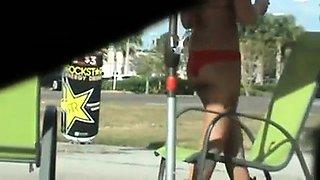 Street voyeur spies on a busty brunette in a sexy red bikini