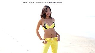 Hot asian model audrey in yellow bikini strips on beach