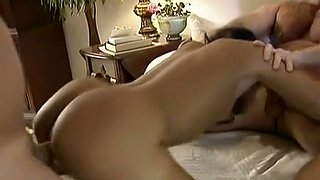 Delicious and submissive brunette with two men on the couch