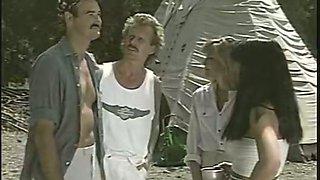 A blonde and a brunette go lesbian in a tent in retro porn clip