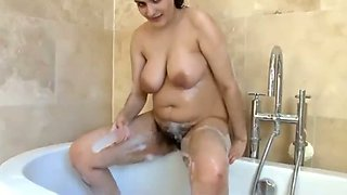 Busty Indian model with hairy pussy in solo action in the bathtub