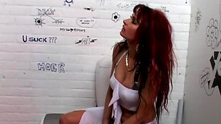 Redhead Natasha sucking a stiff dick coming out of a glory-hole