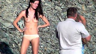 Beach voyeur captures a cute brunette teen with perky boobs