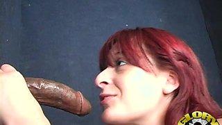 Slutty redhead sucks and strokes a big black cock from a hole