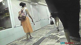 Brunette's skinny ass under mini skirt, in upskirt clip