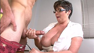 Handsome stud gets his stiff dick tugged by dirty mature Kriss Kelly